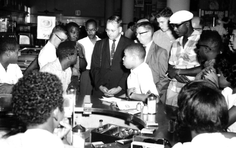 A group of black and white men talking at a lunch counter